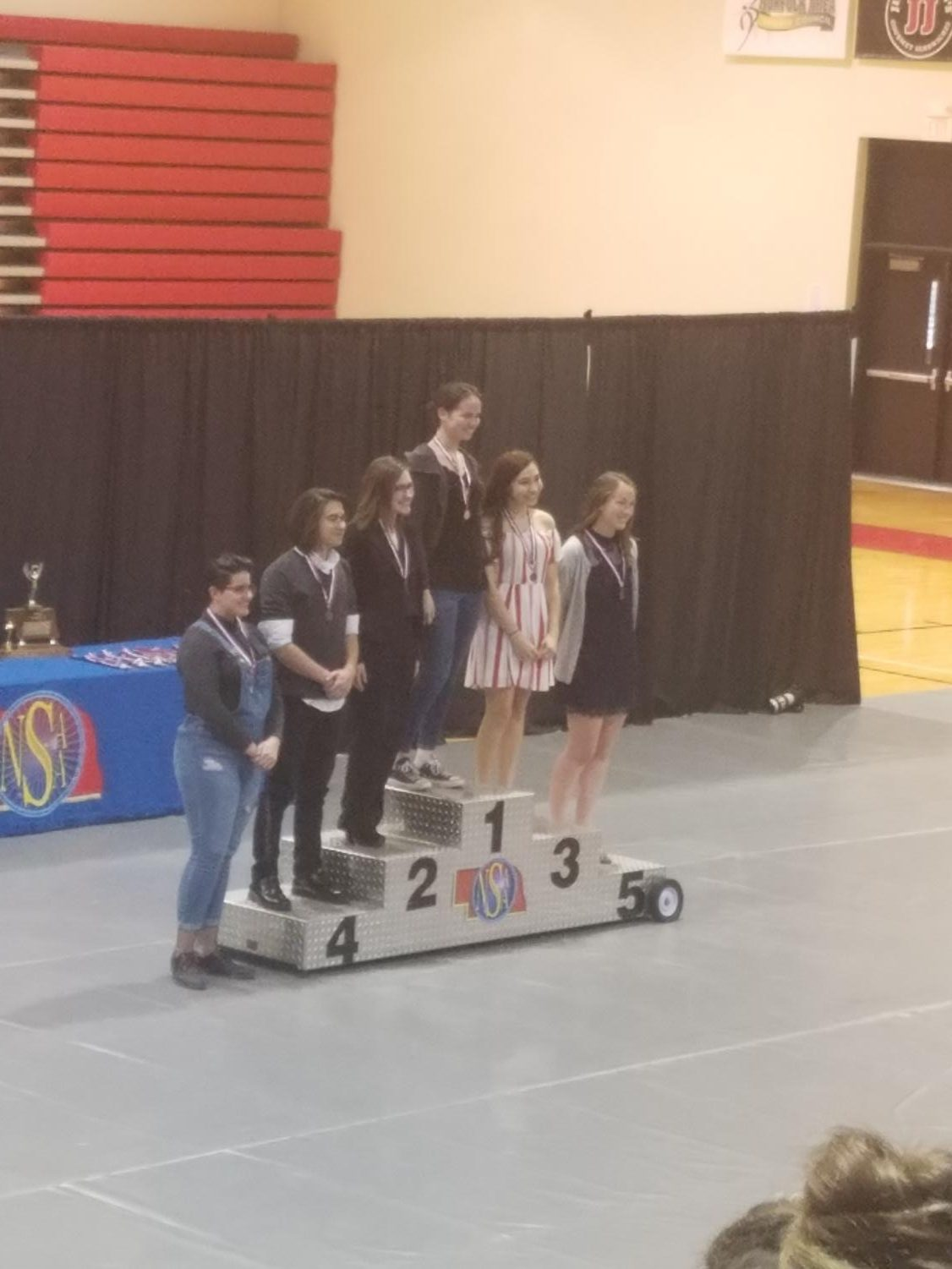 Devon Walter poses for a picture on the podium for first place, standing beside the other students who placed in the top 6 in Layout Design. Photo by Angel Trinh.