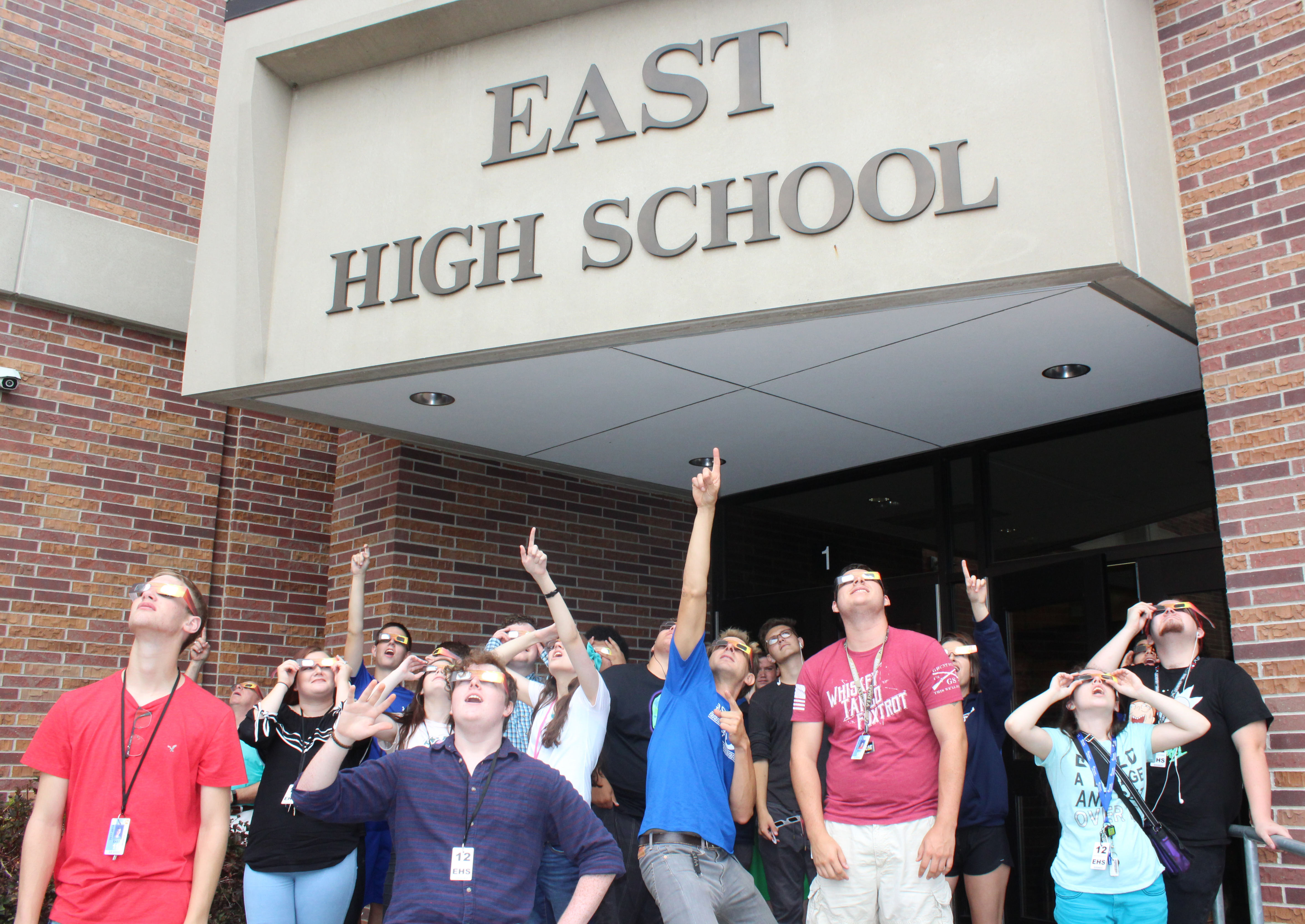 Lincoln East science teacher Mr. Schmidt and his class take a break to gaze at the beginning of the eclipse on Monday, August 21st. All LPS schools took a break to watch the memorable event. Photo by Nick Rippe