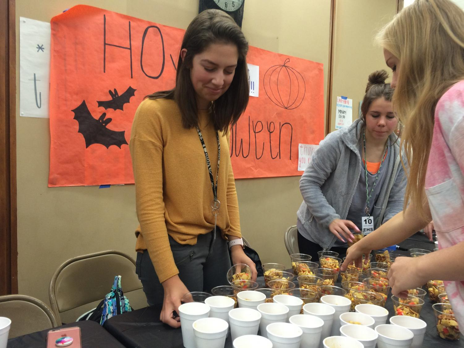 Sydni Springer, Vice President-Elect of the Lincoln East HOSA chapter, organizing snacks for HOSA Halloween on October 31, 2017 outside of the cafeteria.