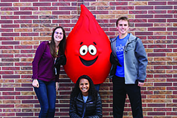 Secretary Isabelle Brundieck, Vice President Laura Francisco, and President Bryan Fitch pose with the bloodbank mascot for their first blood drive that was on Friday, October 27th. Photo by Angel Trinh.