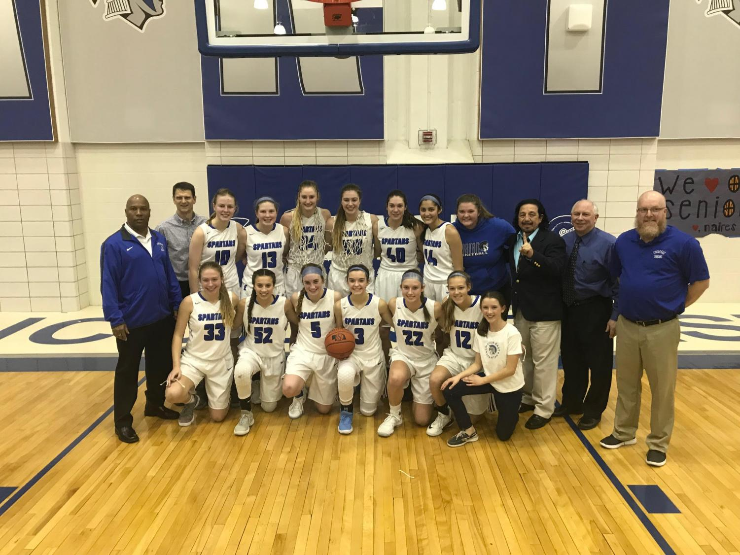 The varsity girls basketball team posses for a picture after winning the A-4 district.