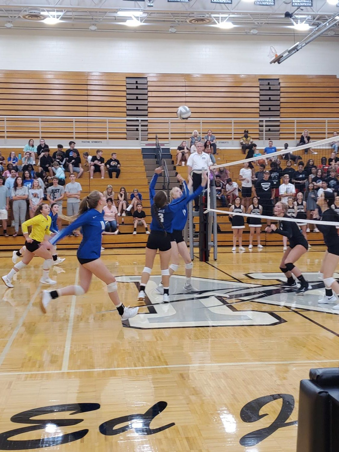 Annalee Ventling-Brown, Julia Holz, and Aleksey Betancur work together to score a point in the first set against Northeast.