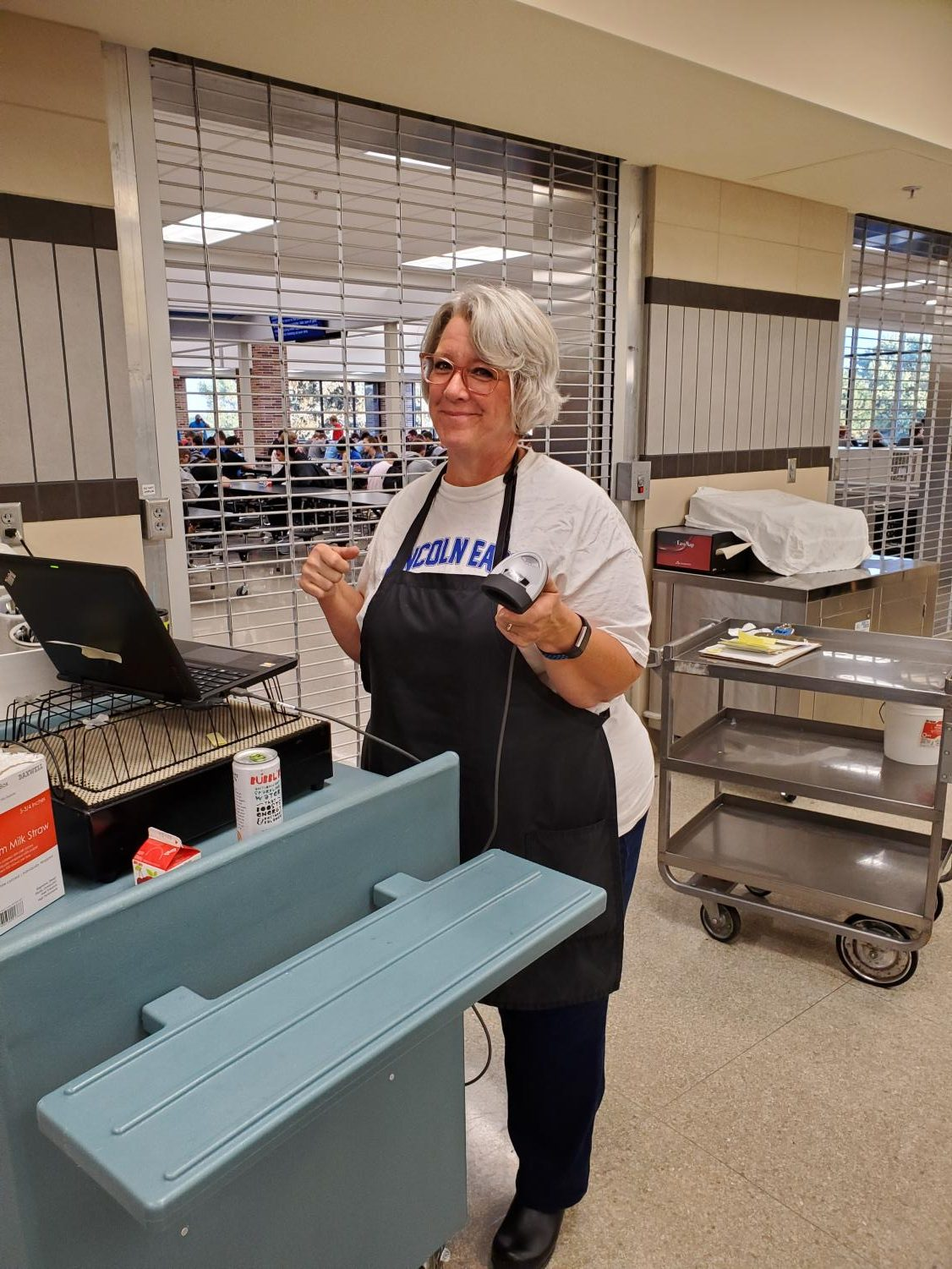 Susan Zander working to serve breakfast to students in the cafeteria before school