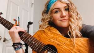 Evy Isom playing her guitar.