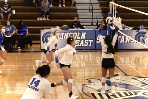 Freshman, Shandy Faalii, setting the volleyball over the net.