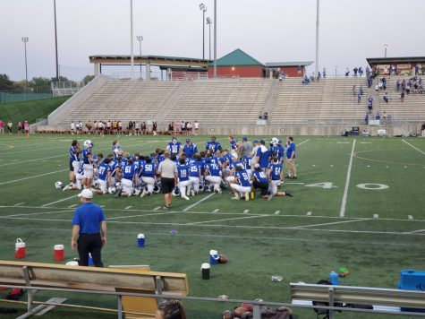 Lincoln Varsity football team huddling after a win against North Platte high school.