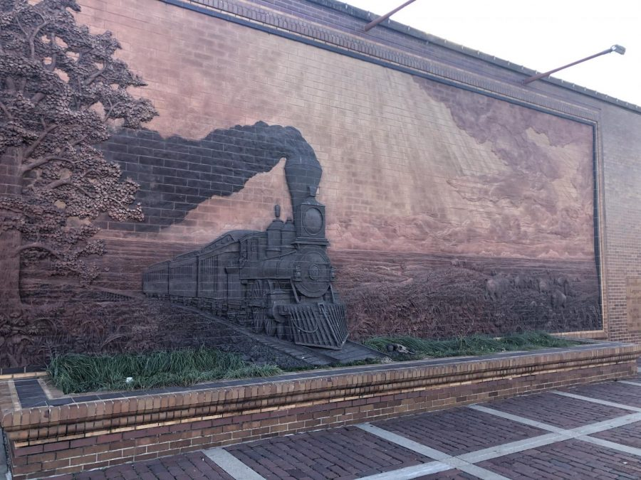 Jay Tschetters 1990 brick mural showcases one of Americas first steam-powered trains, part of the industrialization movement in the 1800s. It is seen passing through a bison herd, grazing in the Nebraska plains.