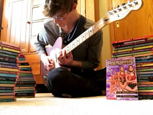Peter Schmit with his guitar & his proud collection of all the Animorphs books.