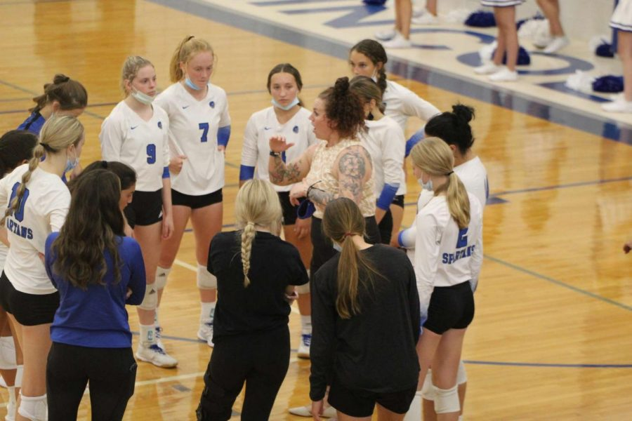 East Spartans Varsity Volleyball team, huddled around Head Coach Nicole Johnson during a time out in their game against Pius X, on Thursday, September 9, 2021. East Spartans lost the game 3-0 to the Pius X Thunderbolts.