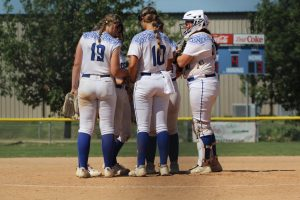 The Lincoln East Varsity softball team huddles at the LPS invite on Saturday August 28th 2021. (L-R) #19 3rd baseman Madison Adams (so), pitcher #10 Jordan Bussey (jr) and catcher Kyndal Colón (sr).