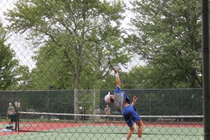 Sophomore Mason Garcia hits a serve at the North Star vs East dual at Woods Tennis Center. Mason Garcia won his 5 Singles match 8-5 towards the beginning of the dual.