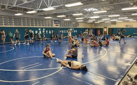 Lincoln East cross country team stretching after practice on Friday, September 3rd. Due to covid 19 athletes are required to wear masks at all times while in the building.