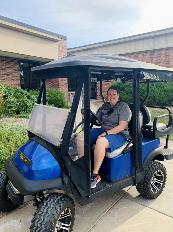 Security guard Abby Hall in the security guard club car in front of the school on September 24. This car is used to transport the security guards from place to place while outside on the East campus.